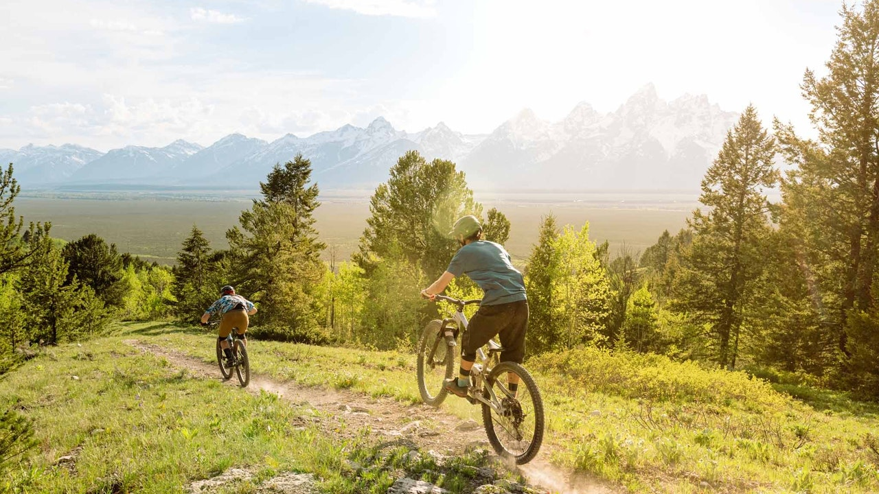 Bikers on a trail with tetons in background