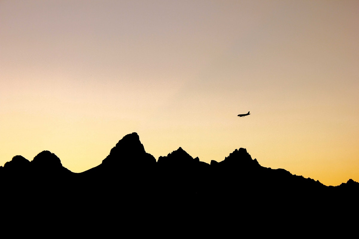 Silhouetted plane flying over mountain peaks