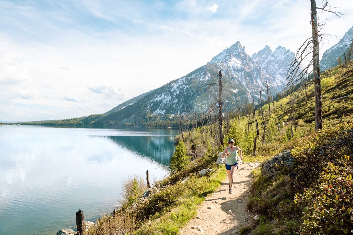 Person running on trail with mountain background